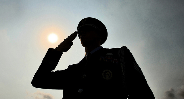 A silhouette of a soldier in dress uniform saluting.