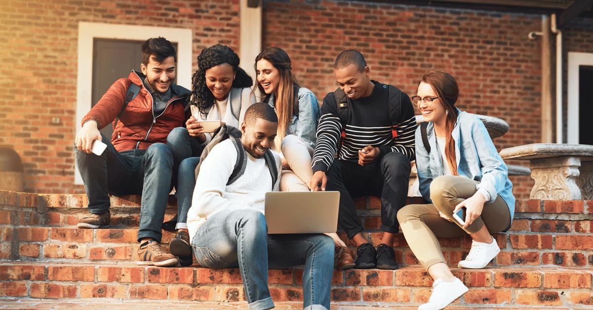 Un groupe de Gén Zers s'est réuni autour d'un ordinateur portable pour bénéficier d'une réduction pour étudiants en utilisant la vérification des étudiants dans le monde entier.